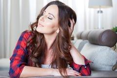 Entspannendes Frauensitzen bequem im Sofaaufenthaltsraum stockbilder