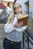 Entspannendes kaukasisches blondes weibliches mit Buch draußen aufwerfen in der Stadt träumen Lizenzfreie Stockbilder