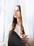 Entspannendes nahes Fenster des schönen Mädchens Dunkles langes gelocktes Haar lizenzfreie stockfotografie