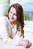 Entspannendes nahes Fenster des schönen Mädchens Dunkles langes gelocktes Haar lizenzfreie stockbilder