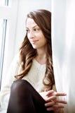 Entspannendes nahes Fenster des schönen Mädchens Dunkles langes gelocktes Haar lizenzfreie stockfotos