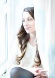 Entspannendes nahes Fenster des schönen Mädchens Dunkles langes gelocktes Haar stockfotos