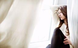 Entspannendes nahes Fenster des schönen Mädchens. Dunkles langes gelocktes Haar stockfoto