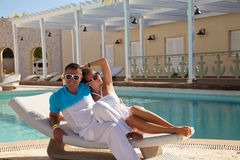 Entspannendes nahes Pool der sexy jungen Paare auf einem Strandbett Lizenzfreies Stockfoto