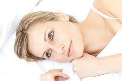 Entspannenlügen der hellen Frau auf ihrem Bett Stockfotos