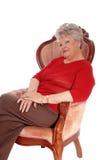 Entspannte ältere Frau, die im Lehnsessel sitzt Stockbilder