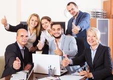 Entspannte Angestellte, die am Schreibtisch sitzen lizenzfreie stockfotografie