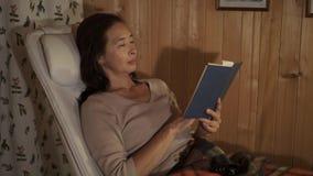 Entspannte Asiatin, die ein Buch im Lehnsessel liest stock video footage