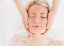 Entspannte blond-haired Frau, die eine Massage erhält Stockbilder