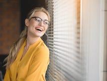 Entspannte blonde Frau, die Ansicht vom Fenster genießt Lizenzfreie Stockfotos