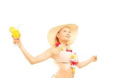 Entspannte blonde Frau im Bikini, der ein Cocktail hält und oben schaut Stockfoto