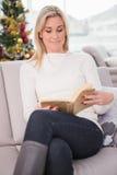 Entspannte blonde Lesung auf der Couch am Weihnachten Stockfoto