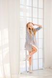 Entspannte Blondine, die nahe großem Fenster stehen Stockfoto