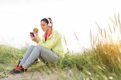 Entspannte Eignungsfrau, die Apfel nach Training isst Stockfoto