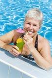Entspannte fällige Frau im Swimmingpool Stockfotos