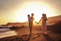Entspannte Familie auf tropischem Strand, schöner Sonnenuntergang Stockfotos
