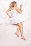 Entspannte Frau, die auf einem bequemen Bett schläft Stockfoto