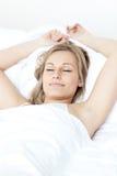 Entspannte Frau, die auf einem Bett schläft Stockfoto