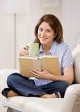 Entspannte Frau, die auf Sofalesebuch sitzt Lizenzfreie Stockfotos
