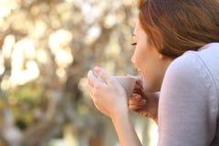 Entspannte Frau, die einen Tasse Kaffee im Freien hält Stockfoto