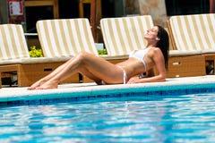 Entspannte Frau, die am ErholungsortSwimmingpool sich bräunt Stockfoto
