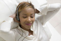 Entspannte Frau, die Musik auf tragbarem CD-Player hört Stockfotografie