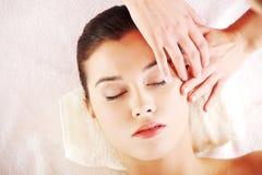 Entspannte Frau genießen, Gesichtsmassage zu empfangen Lizenzfreies Stockfoto