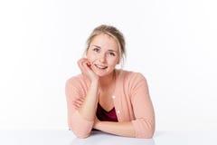 Entspannte Frau im spärlichen Büro lächelnd, um Weichheit auszudrücken Stockbilder
