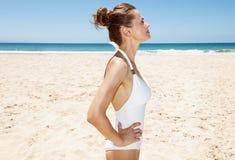 Entspannte Frau im weißen Badeanzug am sandigen Strand Lizenzfreie Stockfotografie