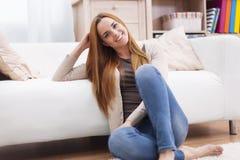 Entspannte Frau im Wohnzimmer Stockbild