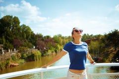 Entspannte geeignete Frau auf Flussboot das Flusskreuzen genießend lizenzfreie stockfotografie