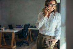 Entspannte Geschäftsfrau, die am Handy spricht stockfoto