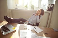 Entspannte Geschäftsfrau mit den Beinen auf dem Schreibtisch Lizenzfreies Stockbild