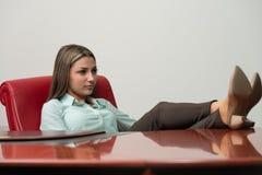 Entspannte Geschäftsfrau mit den Beinen auf dem Schreibtisch stockfoto