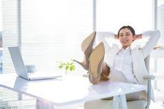 Entspannte Geschäftsfrau, die mit ihren Füßen oben sitzt Lizenzfreies Stockbild