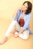 Entspannte gesunde glückliche junge Frau, die auf dem Boden zufrieden gestellt sitzt Stockbilder