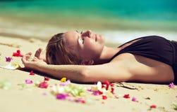 Entspannte junge Frau, die auf dem Sand liegt stockfoto