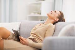 Entspannte junge Frau, die auf Sofa mit Tabletten-PC sitzt lizenzfreie stockbilder