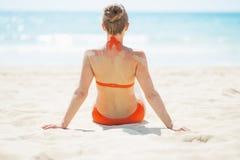 Entspannte junge Frau, die auf Strand sitzt. hintere Ansicht lizenzfreies stockfoto