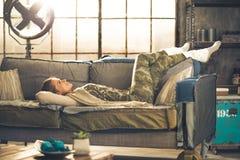 Entspannte junge Frau, die in Dachbodenwohnung legt lizenzfreie stockbilder