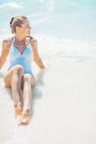 Entspannte junge Frau, die an der Küste sitzt Lizenzfreie Stockfotografie