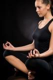 Entspannte junge Frau, die in Lotosstellung trainiert Stockbild