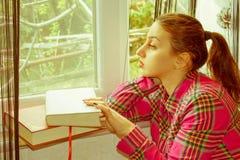 Entspannte junge Frau, die nahe Fenster mit einem Buch sitzt stockfoto