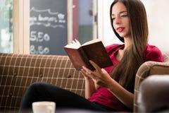 Entspannte junge Frau, die zuhause ein Buch liest Stockbilder