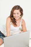 Entspannte junge Frau im Bett mit Laptop Stockfotos