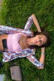 Entspannte junge Frau mit Kopfhörern hörend Musik von einem Smartphone und auf dem Gras liegend, das ihre Augen schlossen Lizenzfreie Stockfotos