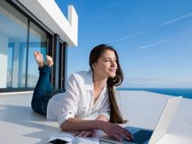 Entspannte junge Frau zu Hause, die an Laptop arbeitet Lizenzfreies Stockbild