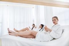Entspannte junge Frauen, die im Wellnessmittelaufenthaltsraum stillstehen stockfoto
