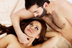 Entspannte junge Paare, die im Bett liegen Lizenzfreie Stockbilder