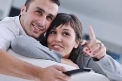 Entspannte junge Paare, die zu Hause fernsehen Lizenzfreies Stockbild